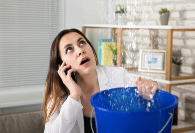 Femme inquiète appelant plombier recueillant des gouttelettes d'eau qui fuient du plafond